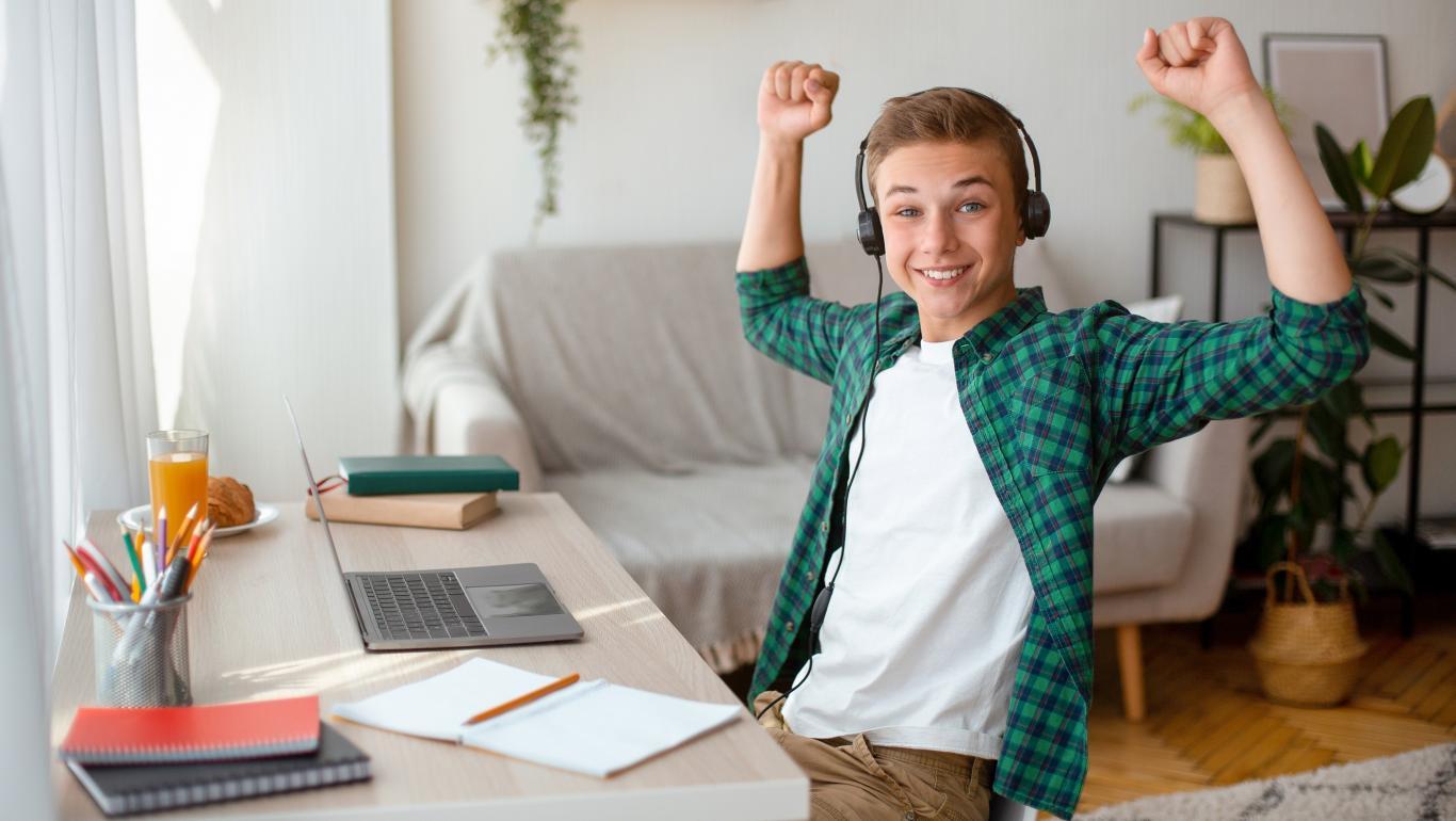 adolescente csentado en mesa con ordenador levantando los brazos