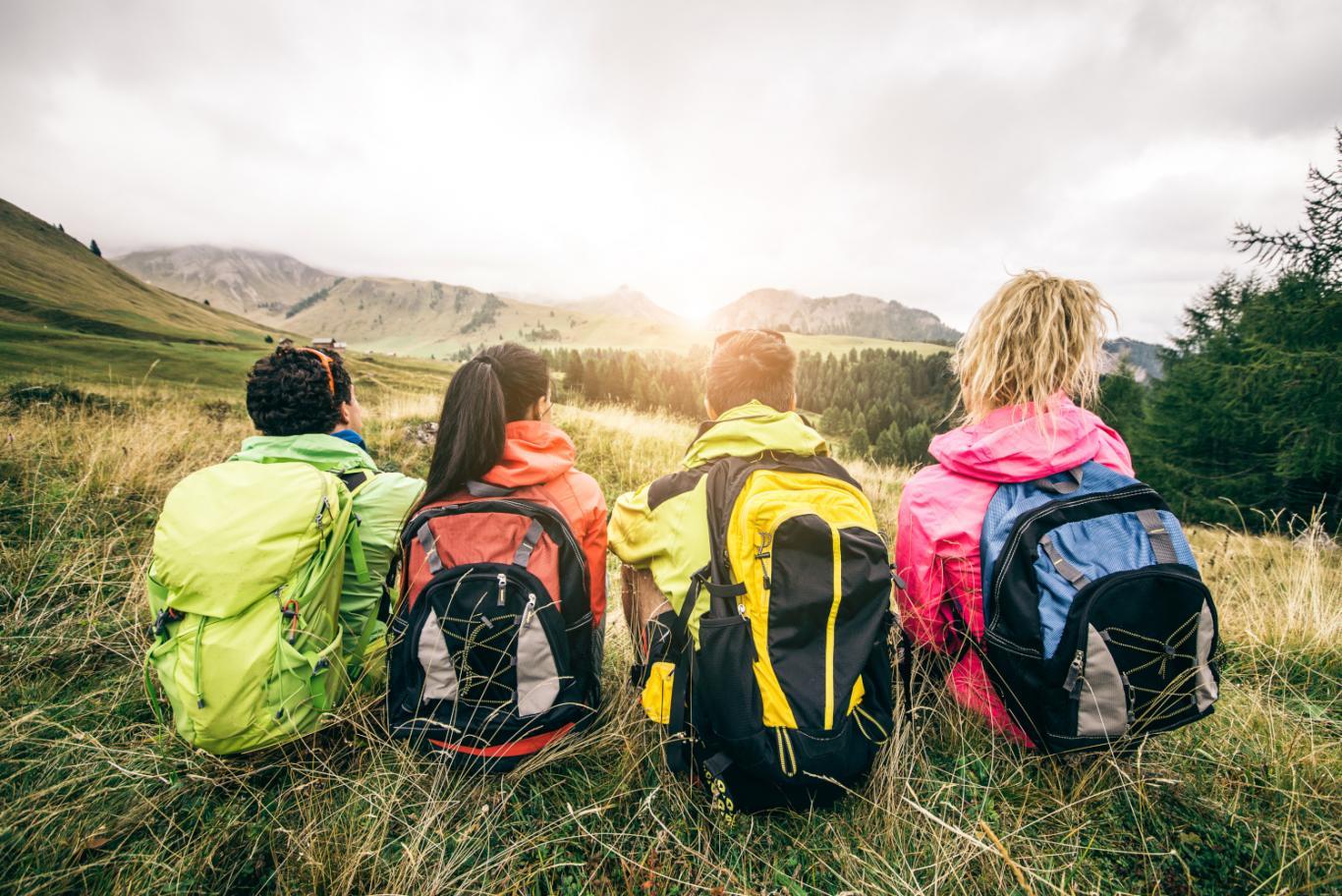 Jóvenes sentados de espaldas con mochilas