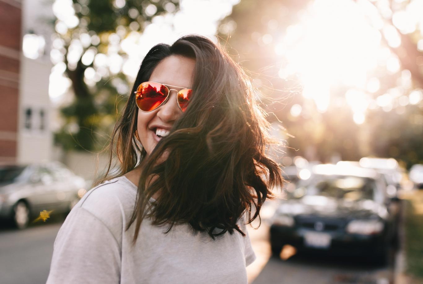 Chica con gafas de sol y pelo suelto sonriendo