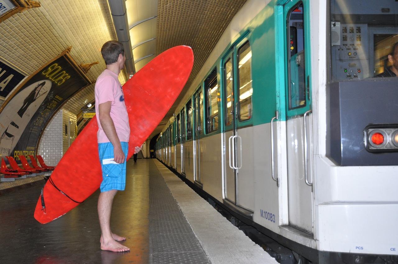 Chico con una tabla de surf roja en el metro