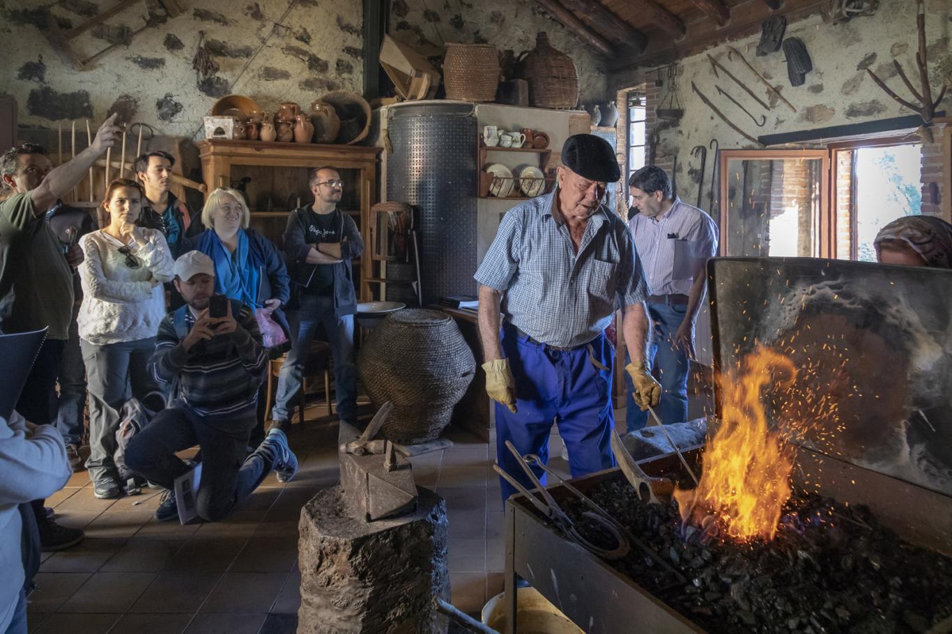 Imagen de grupo de turistas observan a vecino de Villavieja de Lozoya forjando al fuego