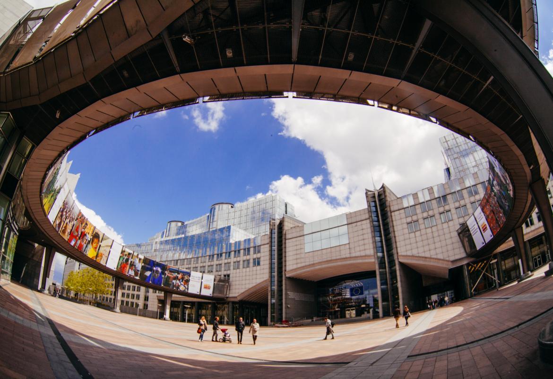 Exterior del edificio del Parlamento Europeo en Bruselas, con un cielo claro con nubes al fondo