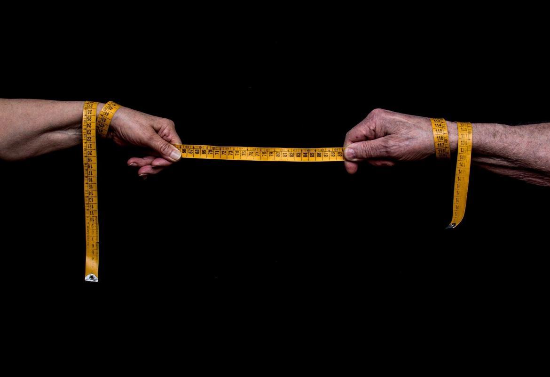 Dos manos sosteniendo una cinta métrica