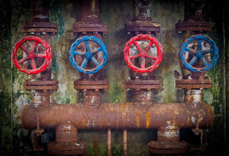Grandes tuberías oxidadas por fuera con cuatro grandes llaves de color rojo y azul