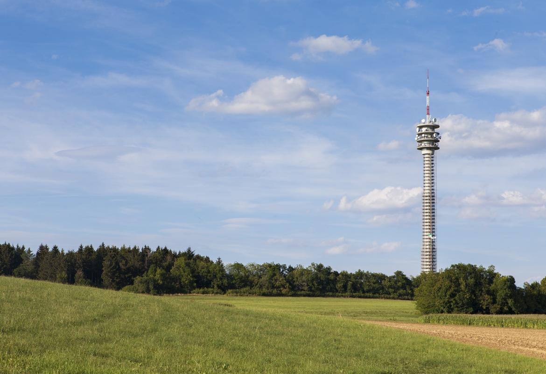 Antena de telefonía móvil alejada de la ciudad, tras un prado verde