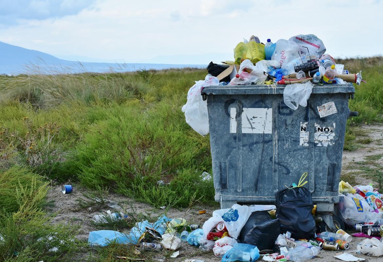 Contenedor de basura lleno y con bolsas rebosando y en el suelo