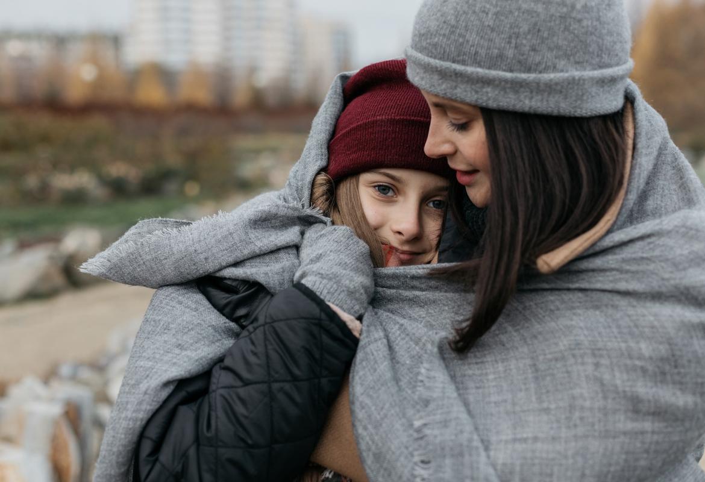 Dos chicas abrazadas y con varias capas de ropa en invierno