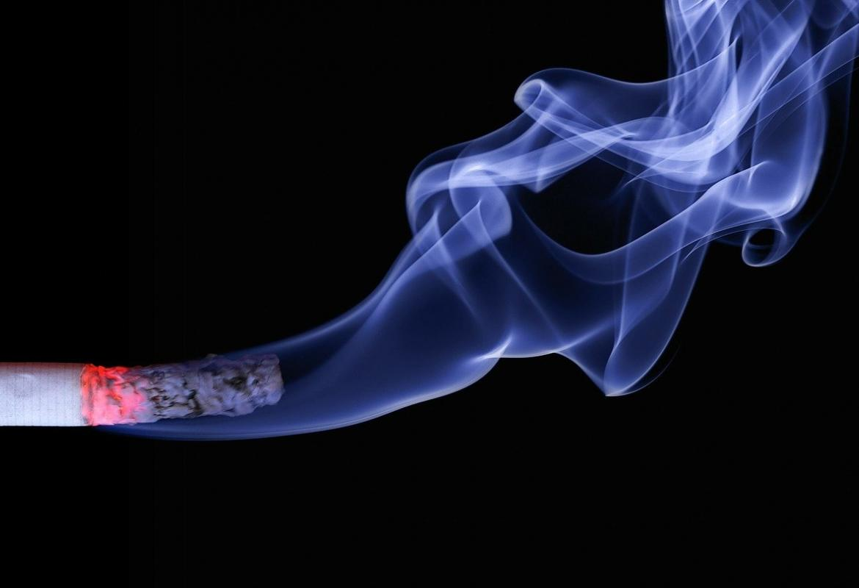 Humo de un cigarro encendido sobre fondo negro