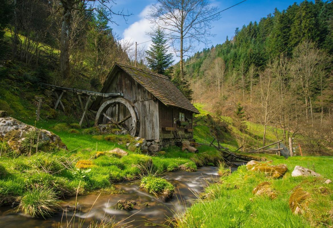 Molino de agua antiguo de madera en el fondo de un valle verde