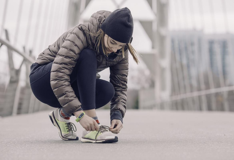 Chica agachada abrochándose la zapatilla de deporte
