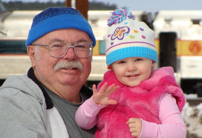 Abuelo con nieta en invierno abrigados y con gorro