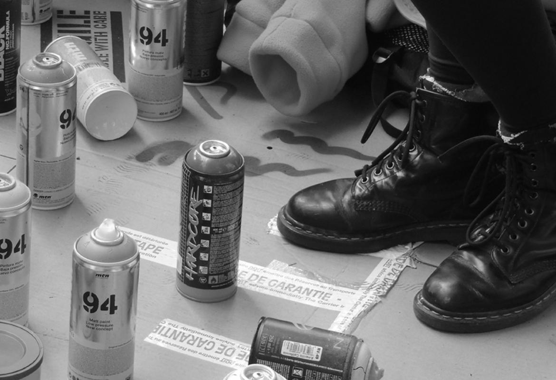 Botes de productos químicos en el suelo a los pies de una persona con botas