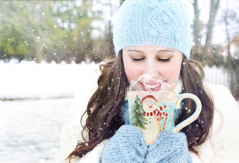 Chica en la nieve con gorro, guantes y una taza de bebida caliente