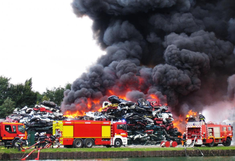 Bomberos apagando un incendio en un desguace de coches con mucho humo