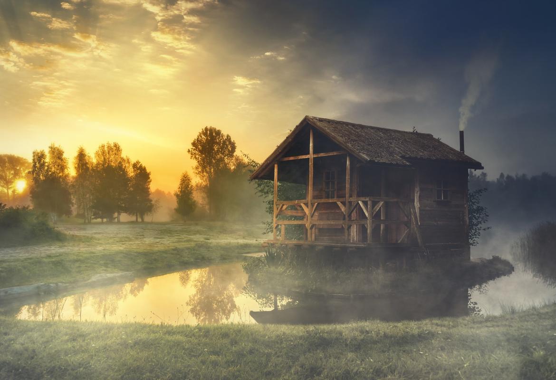 Casa entre niebla en una isleta de un lago