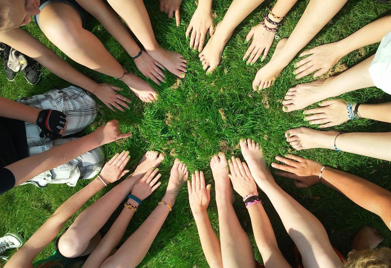 Vista desde arriba de un círculo hecho con manos y pies de jóvenes