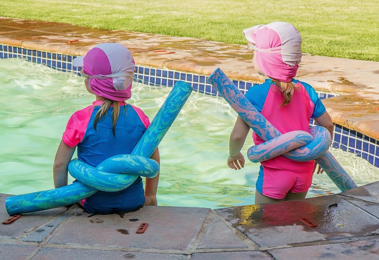 Dos niños de espalda en una piscina, con gorro y flotador