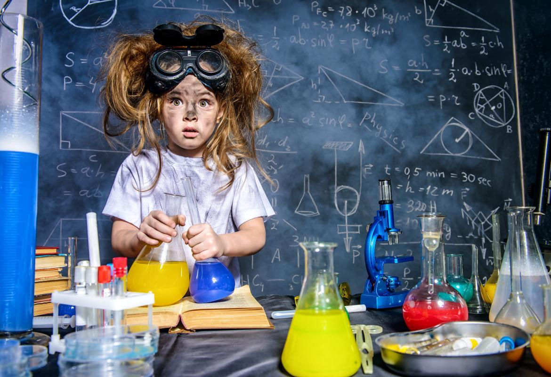 Niña con la cara sucia, gafas de laboratorio en la cabeza y pelos alborotados con matraces en la mano en un laboratorio