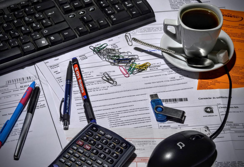 Papeles, teclado, bolígrafos, clips, pen-drive y taza de café sobre una mesa