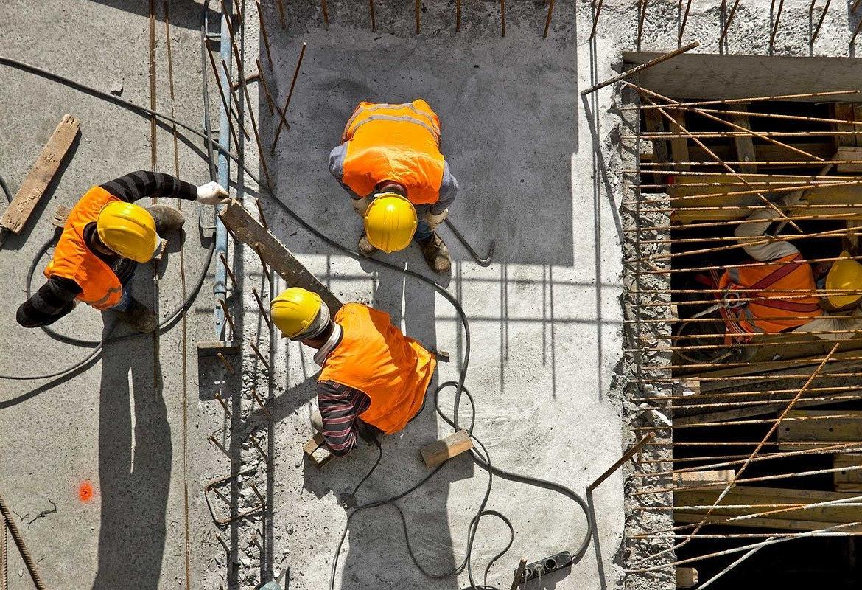 Obreros de la construcción en lo alto de un edificio al sol