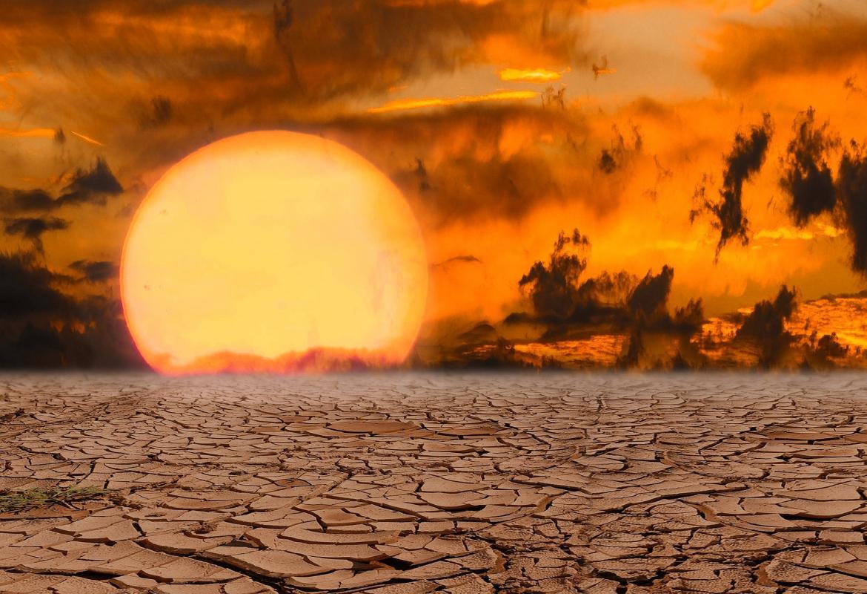 Suelo seco resquebrajado, sol muy grande y nubes rojas