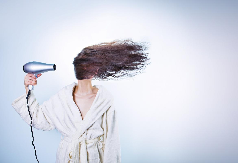 Chica en bata secándose el pelo con un secador de mano