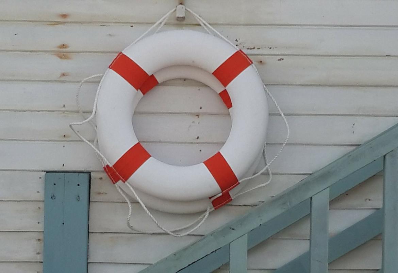 Dos salvavidas colgados en una pared blanca