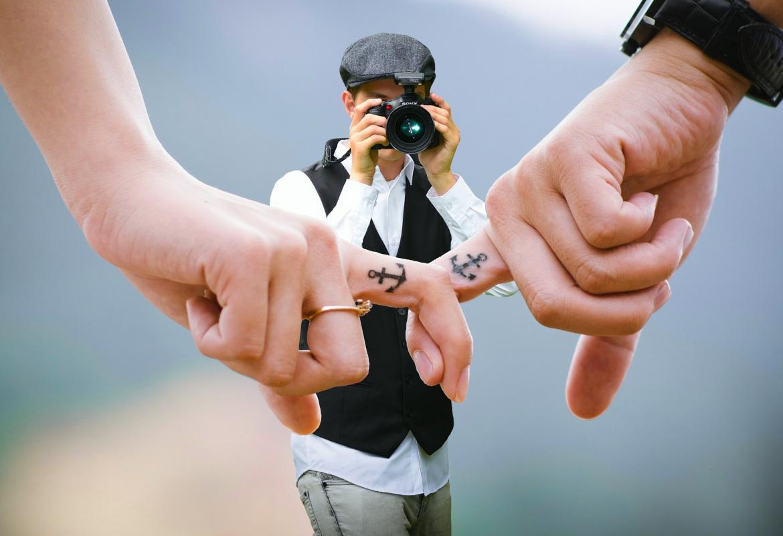 Manos entrelazadas por un dedo con un tatuaje de un ancla siendo fotografiados