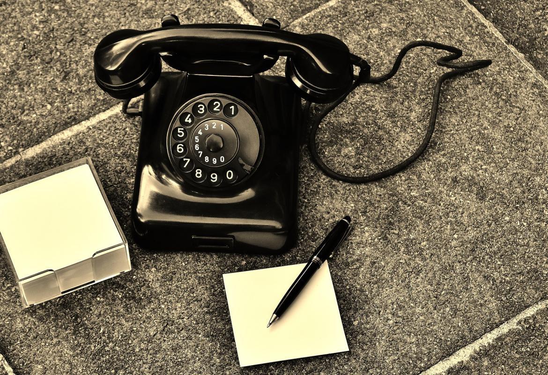 Teléfono antiguo negro de mesa junto a tacos de notas y un bolígrafo