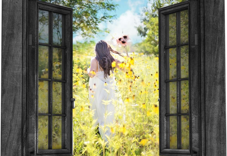 Ventana de una casa abierta a través de la que se ven flores y una mujer