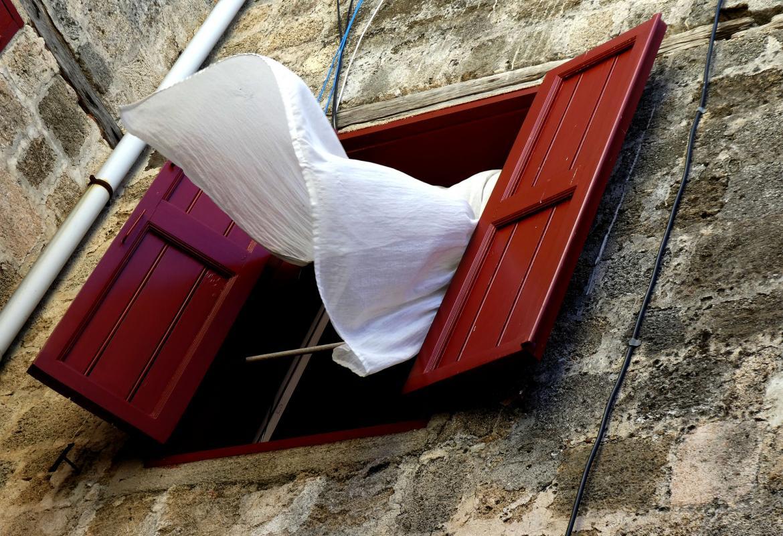 Fachada de una casa antigua con las ventanas abiertas y la cortina moviéndose por el viento