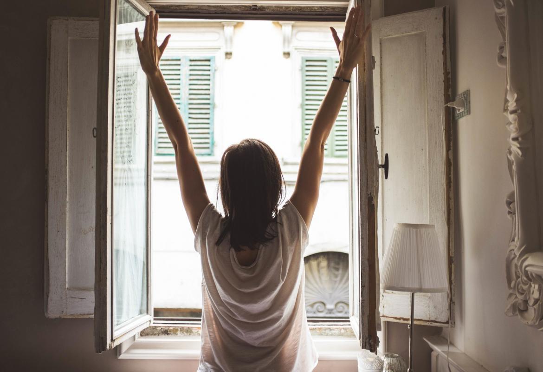 Chica de espaldas con los brazos levantados frente a una ventana de un domicilio abierta