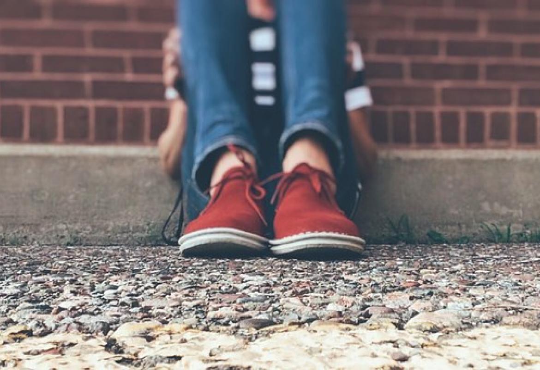 Chico sentado que solo se le ven zapatos