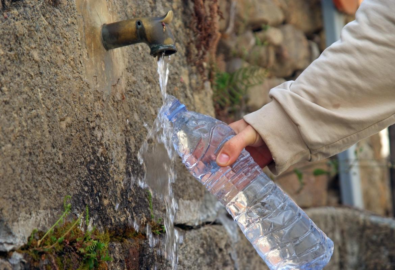 Persona rellenando una botella en una fuente