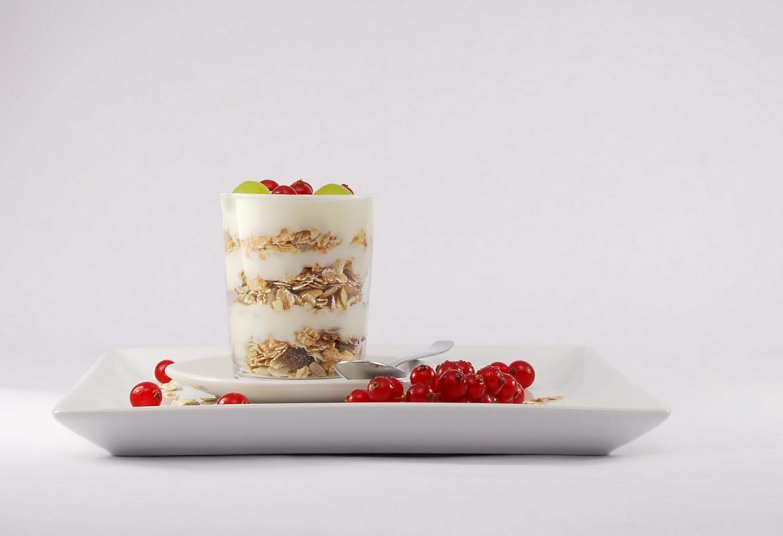 plato con frutos rojos y un vaso con yogur, cereales y frutos