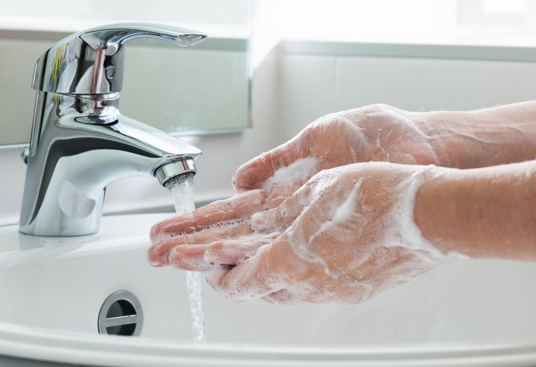 Manos lavándose las manos con jabón bajo un grifo