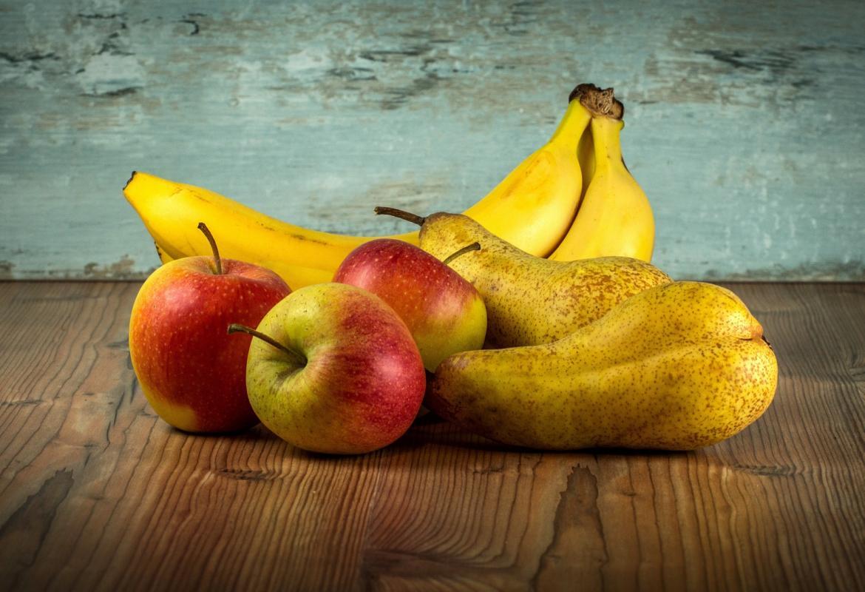 pera, plátano y manzanas sobre una mesa de madera