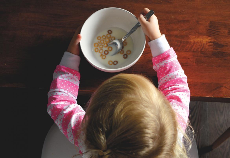 Niña comiendo un bol con leche y cereales