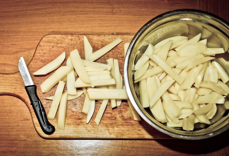 Patatas cortadas con pelador sobre una tabla de cortar