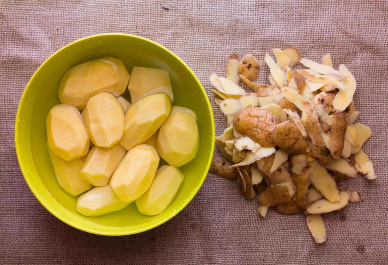 Cuenco con patatas enteras peladas, y piel separada del cuenco