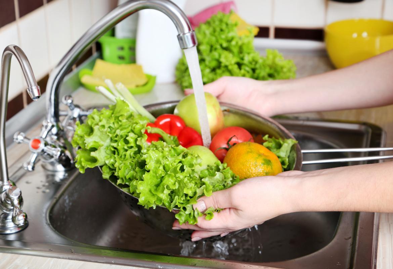 Lavando varios vegetales bajo el grifo