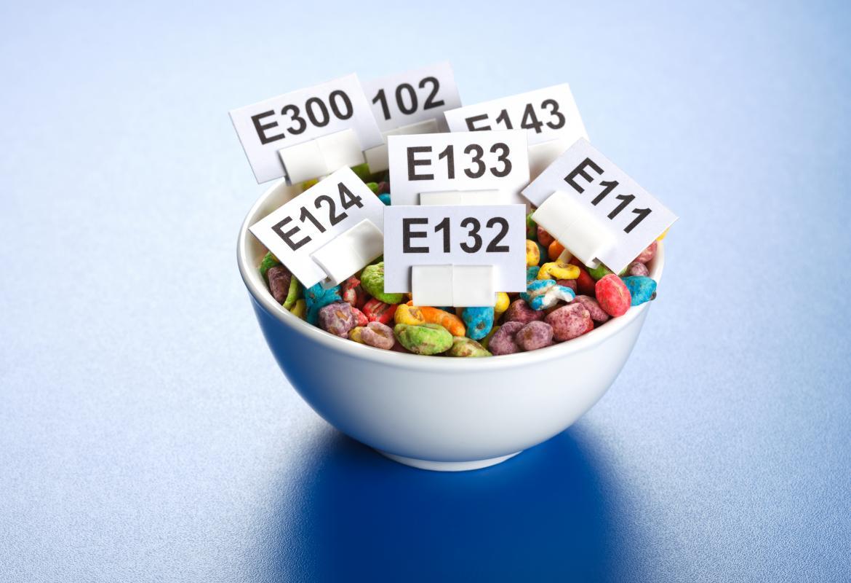 Taza de alimentos (caramelos de colores) con carteles que identifican los aditivos alimentarios que contienen