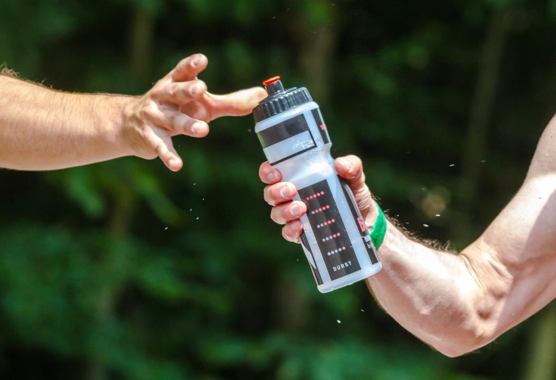 deportistas pasándose botella de agua