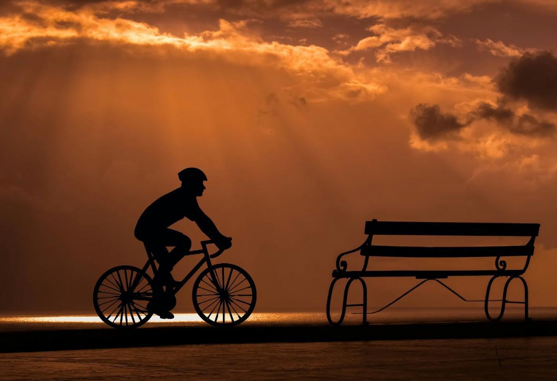 ciclista llegando a un banco al atardecer