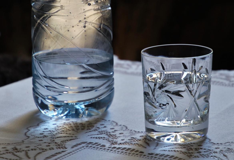 vaso de agua con botella al lado
