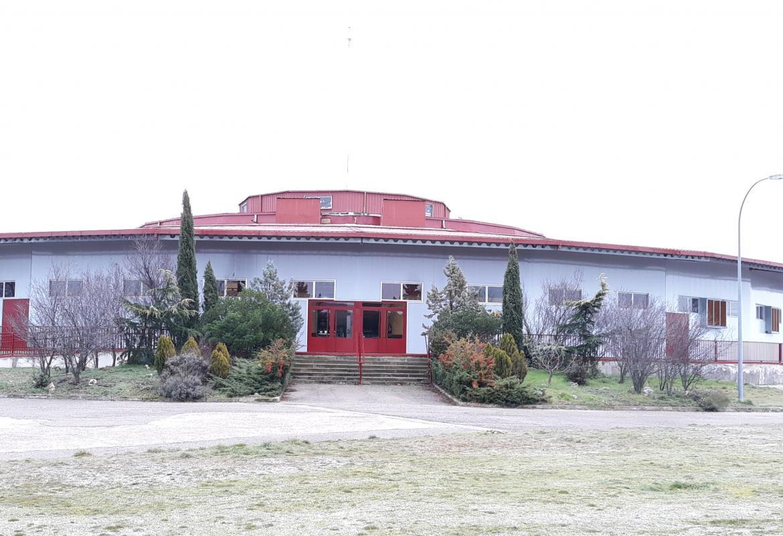 Fachada del edificio del recinto ferial del IMIDRA con puertas y tejado rojo, con acceso mediante escalones.