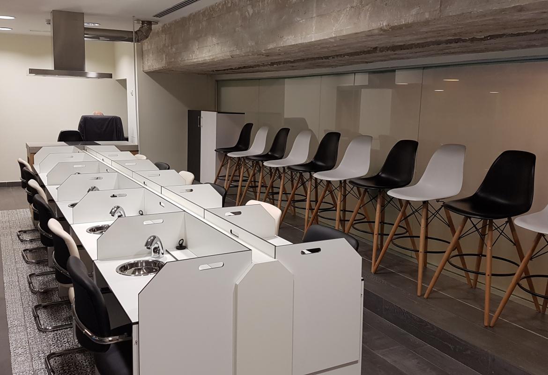 Sala de catas de productos alimentarios con cabinas de análisis sensorial en color blanco y asientos en blanco y negro de modo alterno