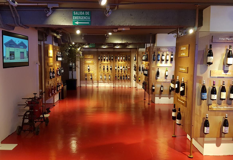 Botellas de la DO Vinos de Madrid enganchadas de modo individual a varios paneles formando hileras