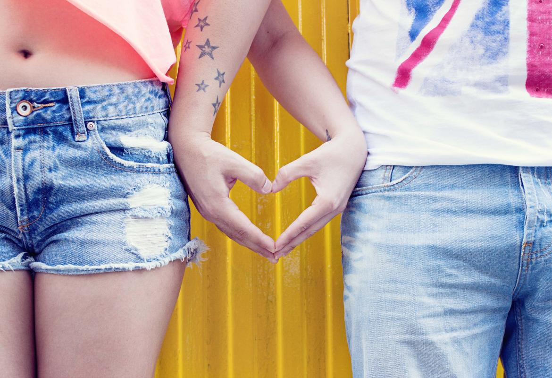pareja haciendo con sus manos y brazos un corazón