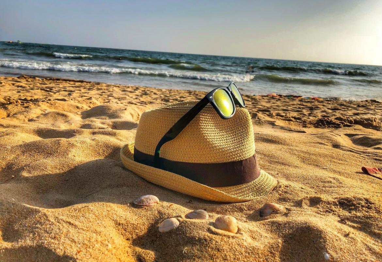 Sombrero y gafas sobre arena de playa